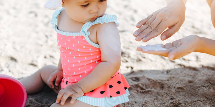 applying sun lotion to baby
