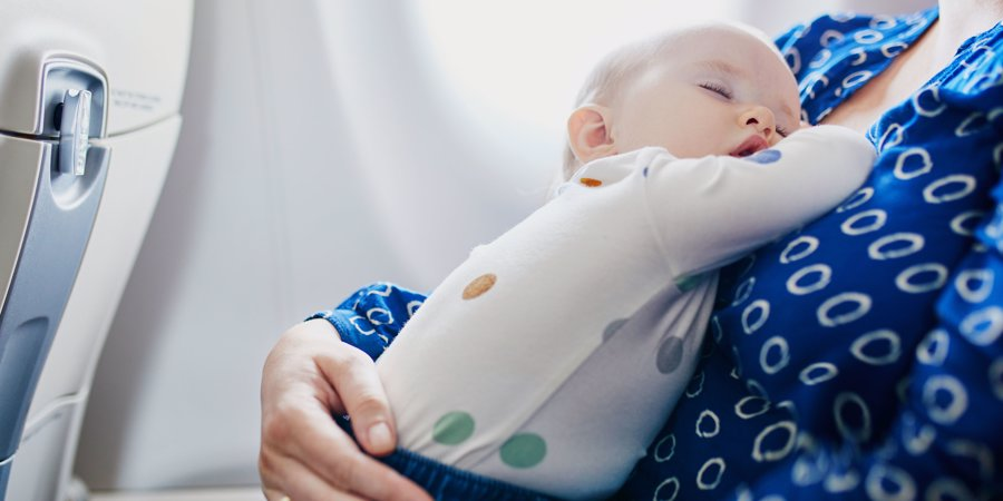 baby asleep on mother aboard a plane
