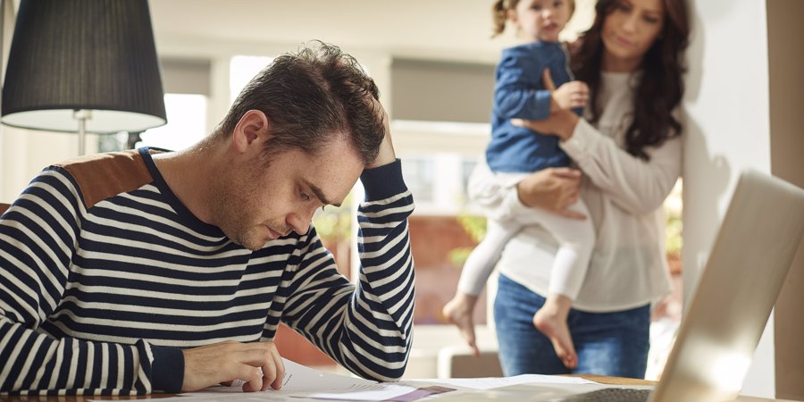 dad stressed with work while mum and child stands beside him