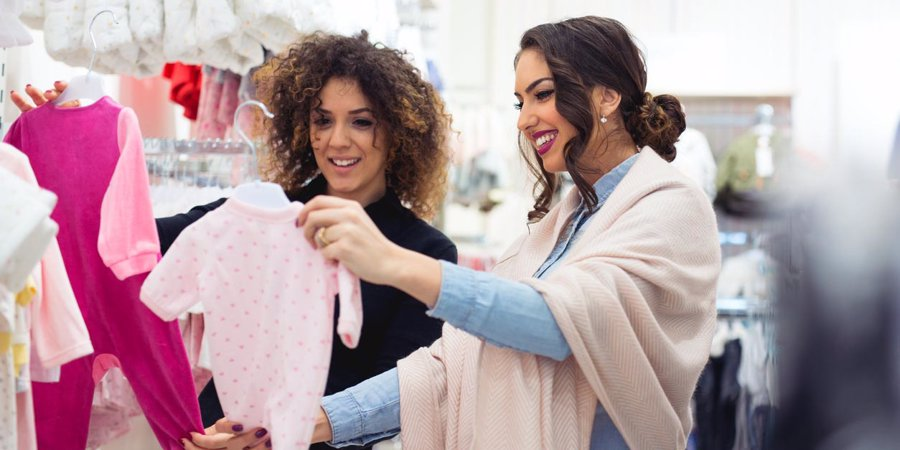women picking out baby girl clothes